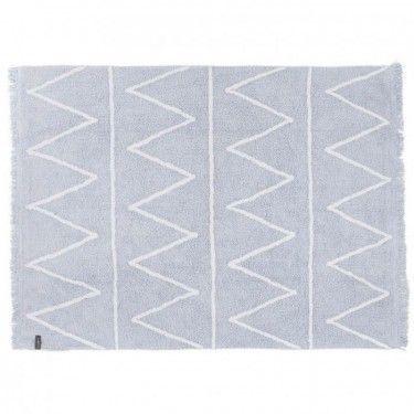 Alfombra azul claro con zigzag blanco y flecos.
