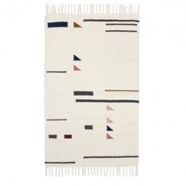 Alfombra blanca con flecos y motivos geométricos de colores.