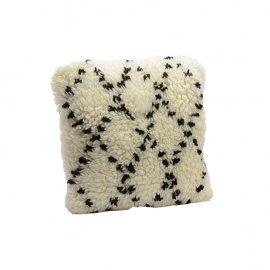 Cojín de lana blanca con rombos negros.